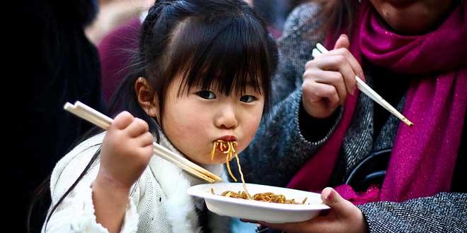 Niña japonesa a quién su madre da de comer