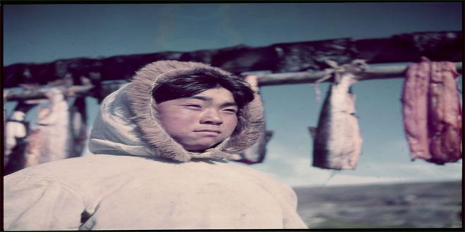 Muchacho inuit. Detrás pueden observarse trozos de pescados puestos a secar