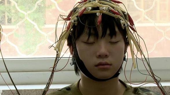 niño chino con cables en la cabeza